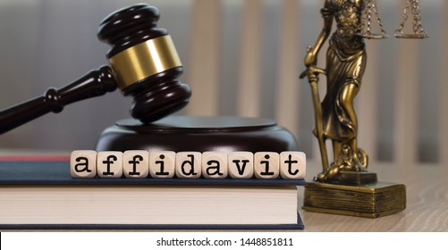 Word AFFIDAVIT  composed of wooden dices. Wooden gavel and statue of Themis in the background. Closeup