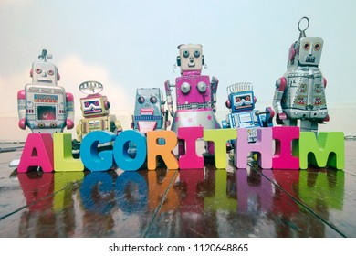 the word ALGORITHIM  with wooden letters and retro toy robots  on an old wooden floor with reflection