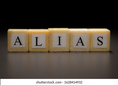 The word ALIAS written on wooden cubes isolated on a black background
