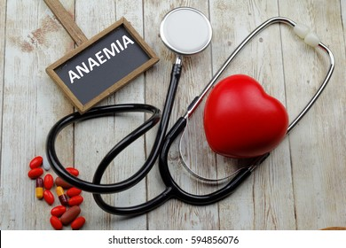 Word Anaemia written on blackboard with stethoscope, medicine and heart shape symbol on wooden background.