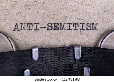 The word anti-semitism written in typewriter font. The inscription in the old style on gray paper. Grey background.
