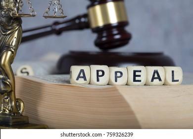 Word APPEAL bestehend aus Holzbriefen. Statue von Themis und Richter-Avel im Hintergrund