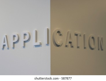 """The word """"application"""" embossed on a white wall, partially blurred"""