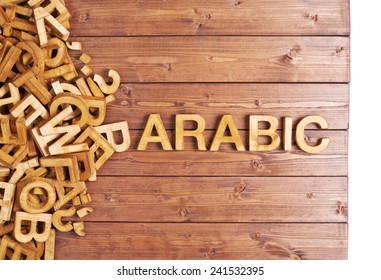 Word arabic made with block wooden letters next to a pile of other letters over the wooden board surface composition