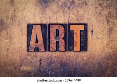 "The word ""Art"" written in dirty vintage letterpress type on a aged wooden background."
