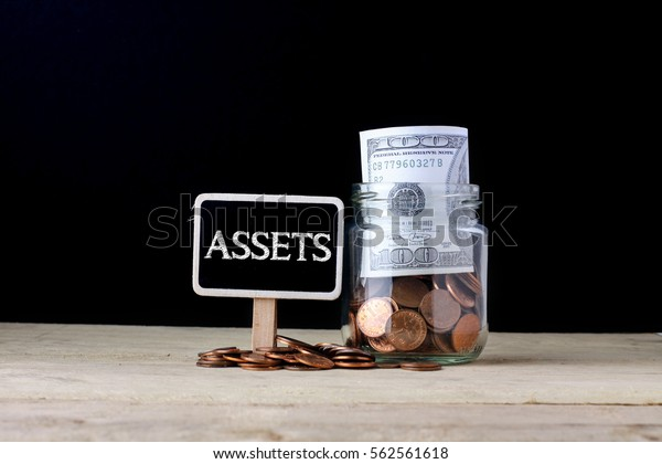 Word ASSETS on chalkboard with money on glass