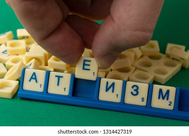 """Word """"ATHEISM"""" on  russian language written with Scrabble letters with man fingers, composing a word"""