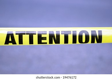 "Word ""Attention"" on yellow tape"