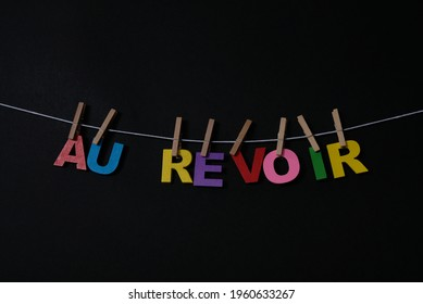 Word Au Revoir on black background. Au Revoir  means good bye in French. Concept for art, learning, and education.