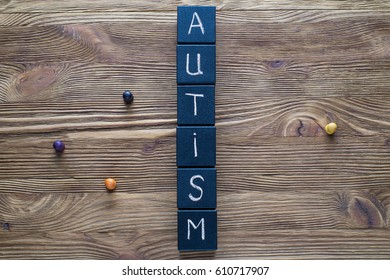 Word Autism built of black wooden blocks on a wooden background with copy space, top view, flat lay. Concept of autism word, flat lay. Autism Spectrum Disorder (ASD).  Autism awareness.