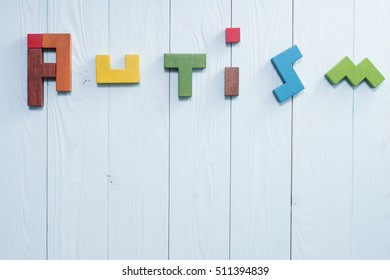 Word Autism built of colorful wooden blocks on a blue wooden background with copy space, top view. Concept of autism word, flat lay. Autism Spectrum Disorder (ASD).