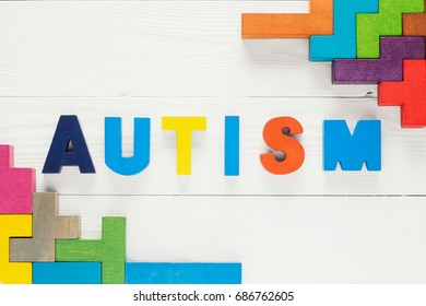Word Autism built of colorful wooden blocks on a white wooden background with copy space, top view. Concept of autism word, flat lay. Autism Spectrum Disorder (ASD).