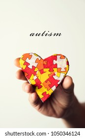 the word autism and a heart patterned with many puzzle pieces of different colors, symbol of the autism awareness, in the hand of a young caucasian man, against an off-white background
