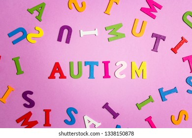 The word autism and multi-colored letters on a purple background. Autism Awareness Day. Autism Spectrum Disorder (ASD) concept.