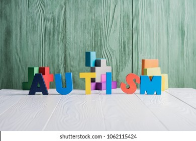 Word AUTISM with a pieces of puzzle on white wooden background. Autism Spectrum Disorder (ASD) concept. Autism awareness.