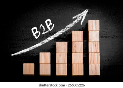 Word B2B on ascending arrow above bar graph of Wooden small cubes isolated on black background. Chalk drawing on blackboard. Business Concept image.
