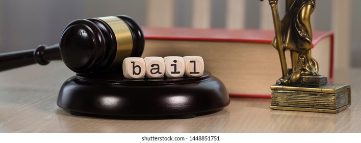 Word BAIL composed of wooden dices.  Wooden gavel and statue of Themis in the background. Closeup