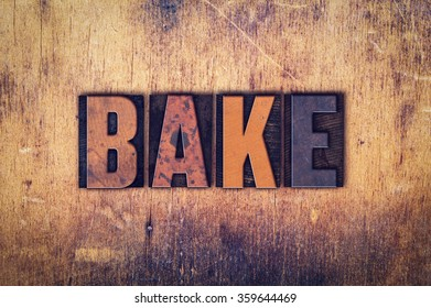 "The word ""Bake"" written in dirty vintage letterpress type on a aged wooden background."