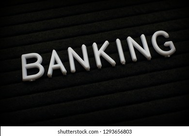 The word Banking in white plastic letters on a black letter board