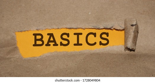 The word Basics appearing behind torn brown paper. Education concept.