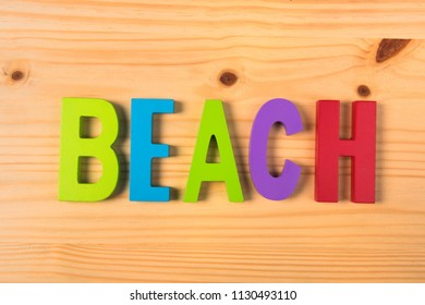The word beach in colorful wooden letters on wood
