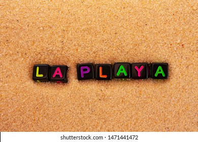 The word beach (in spanish la playa) is composed of colored letters on black cubes and lie on the sand.