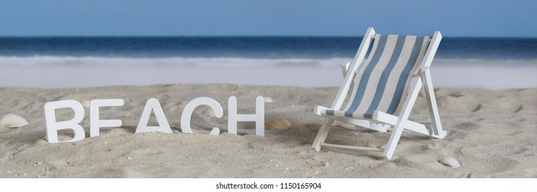 The word beach in white wooden letters in the sand on the beach, banner
