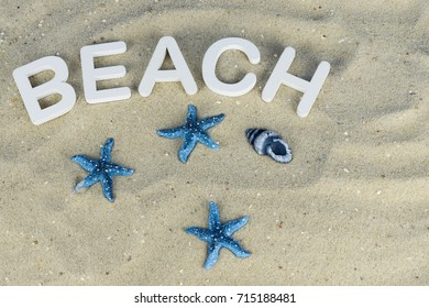 The word beach in white wooden letters in the sand on the beach