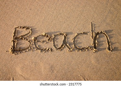 The word beach, written in sand.