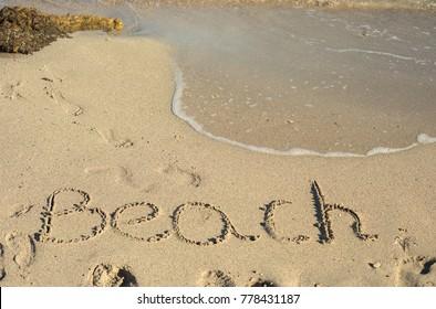 The word beach written in the sand on a beach