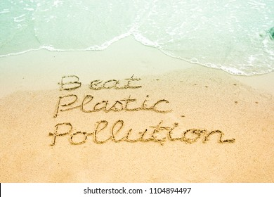 The word Beat Plastic Pollution, a campaign for the World Environment Day 2018, hand written on sandy beach background.
