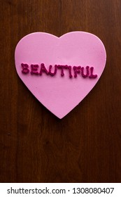 the word beautiful in glitter letters on a pink heart stuck on a wooden cabinet