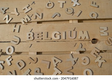 Word Belgium made of wooden block letters on the background of other letters above the composition of the surface of the wooden board