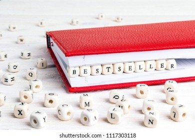 Word Bestseller written in wooden blocks in red notebook on white wooden table. Wooden abc.