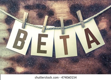 """The word """"BETA"""" stamped on cards and pinned to an old piece of twine over a rusted metal background."""