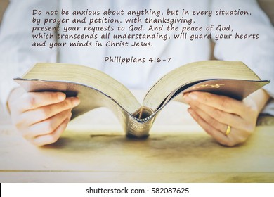 word from bible verses Philippians 4:6-7  over image of woman hold and reading bible on wooden table, trust concept, christian background