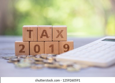 """Word block """"TAX"""", and """"2019"""" on pile of coins with calculator as background. Income, expenses, tax, financial data."""