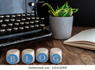 word BLOG on wooden blocks against vintage typewriter, potted plant and note pad on table