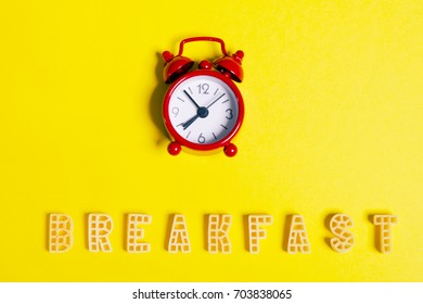"""Word: """"breakfast"""" and a red alarm clock on a yellow background"""