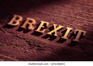 The word BREXIT out of cut wooden letter blocks on old wooden surface