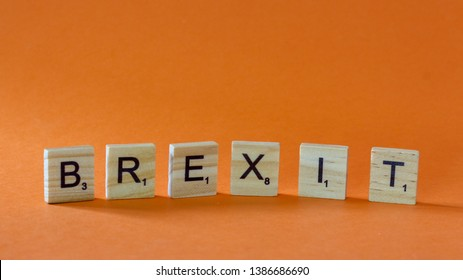 Word BREXIT written on Scrubble letters isolated on orange background. Brexit is shortcut from (Great) Britain exit (Europan Union). Editorial image, studio shot, macro photography, close up photo.