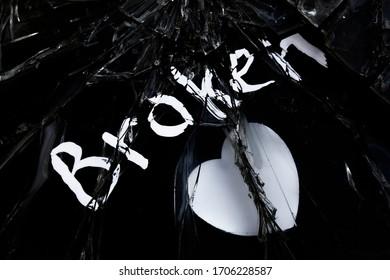 "Word ""broken"" and white heart on shattered dark glass surface, broken heart concept"