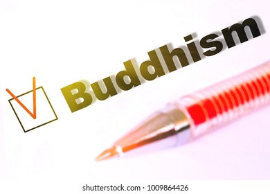 The word Buddhism with a mark in front of a white background with a pen next to it