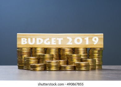 Word budget 2019 with multiple stacked gold coins on dark background.