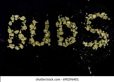 The word Buds spelled out in marijuana on black space like background