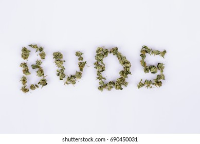 The word buds spelled out with marijuana buds on white background