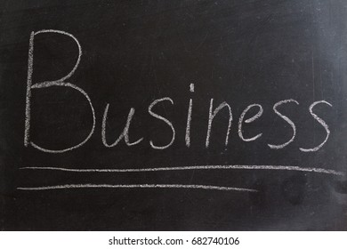 """The word """"Business"""" in chalk on a blackboard. Business and finance."""
