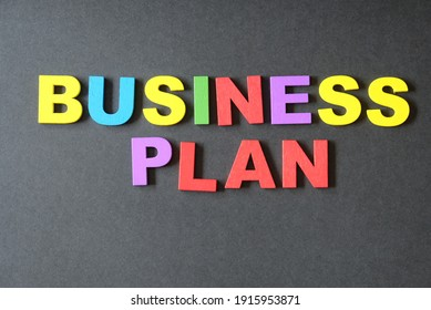 Word business plan on black background. Concept for business and art.