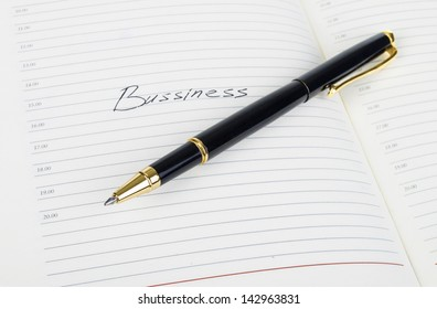 """A word """"bussiness"""" is written on a note pad."""