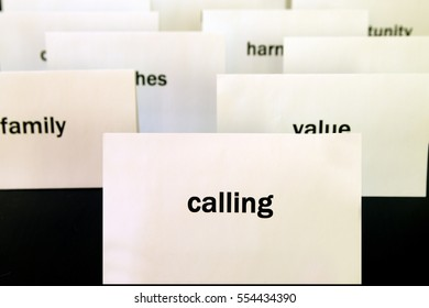 Word Calling on a white paper card surrounded by other words. Priorities and values concept